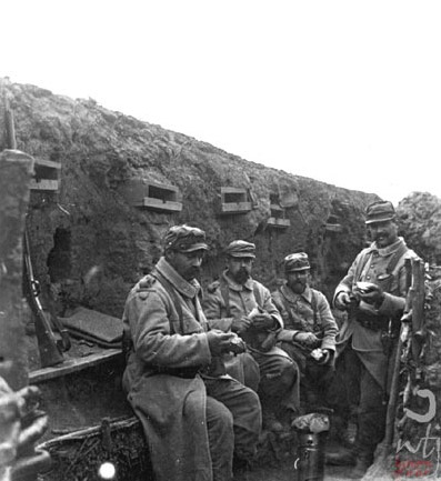 Soldiers sit down for a meal in the trench.
