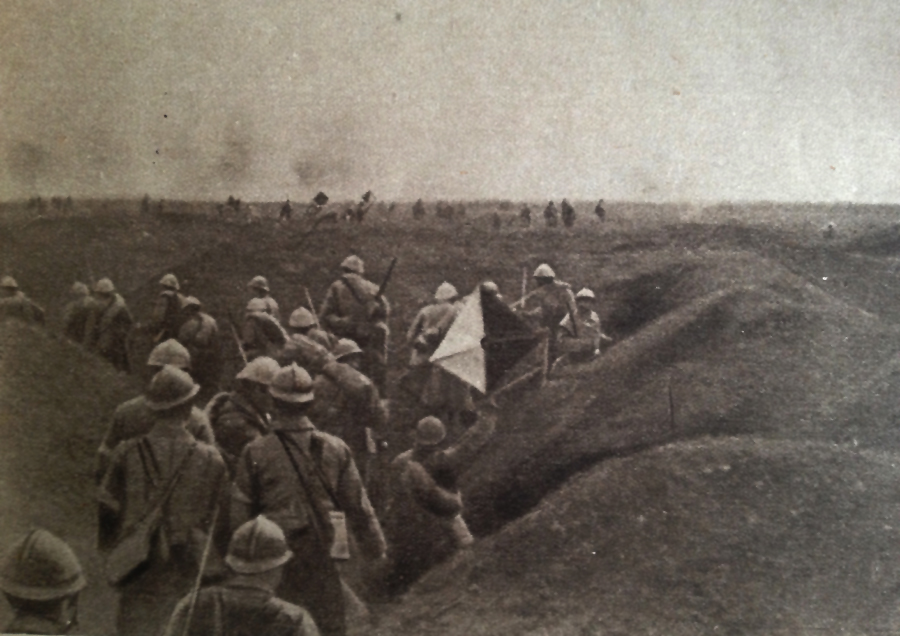 Photo taken during the assault on Dompierre (Somme) 1 July 1916. The second wave waits in a trench with the first waves visible in the distance. The man on the right holds a semaphore and additional signal men can be seen in the distance marking the progr