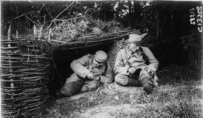 Two soldiers making trench rings in their spare time in front of their shelter.