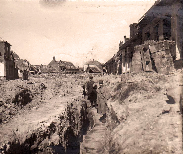 A trench cuts through the street of a devastated village, ca. 1915.