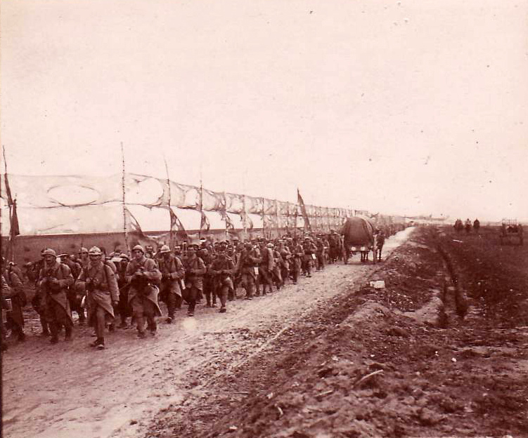 A regiment marched along a road camouflaged be canvas screens near Glennes.