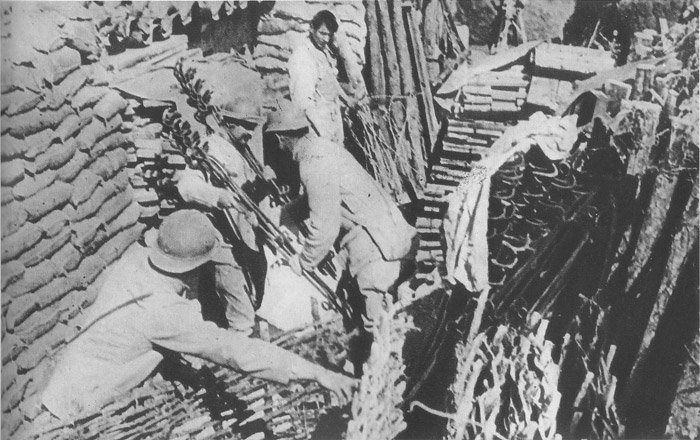 A supply dump in a support trench--sections of wattling, sandbags, iron barded-wire stakes.