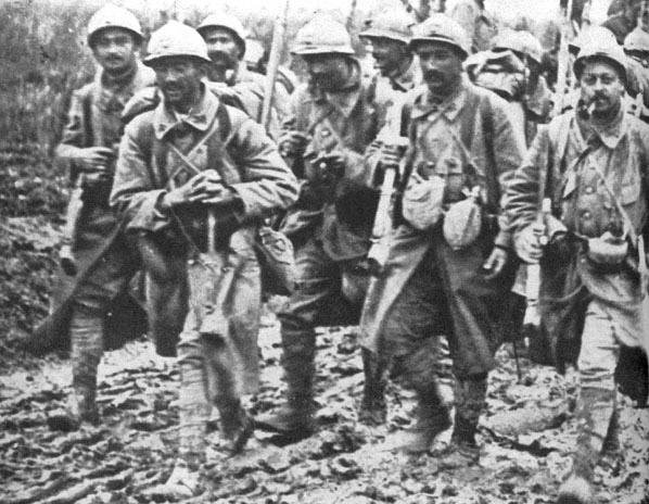 Soldiers coming out of Verdun, 1916. Note the soldiers carrying a German stick grenade and canteen.