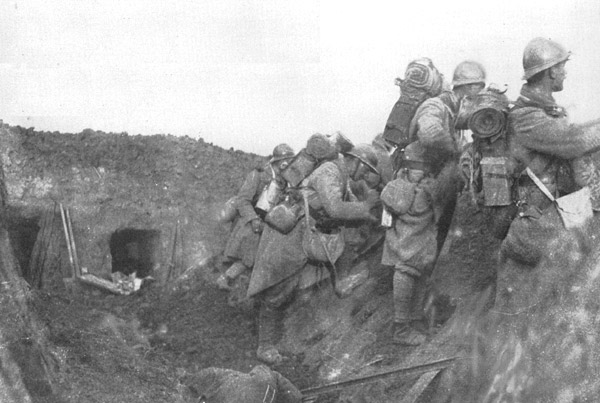 Soldiers man the parapet of a recently conquered trench amid debris and a German corpse.