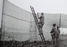 Canvas netting is erected along a roadway to prevent aerial observation as part of the preparations of the Chemin-des-Dames offensive. Photo taken by Frantz Adam, near Villers-Franqueux, March 1917.
