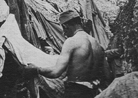 A soldier combs his clothes for lice beside his trench shelter.
