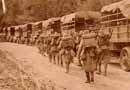 Troops march by a idle convoy of trucks.