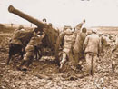 Artillerists struggle through the mud to haul up their gun, a 120 'long.'