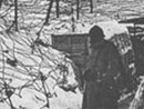 A soldiers stands in a snowy trench completely covered with barbed wired.