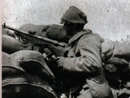 A Chauchat gunner has improvised camouflage for his helmet using a sandbag.