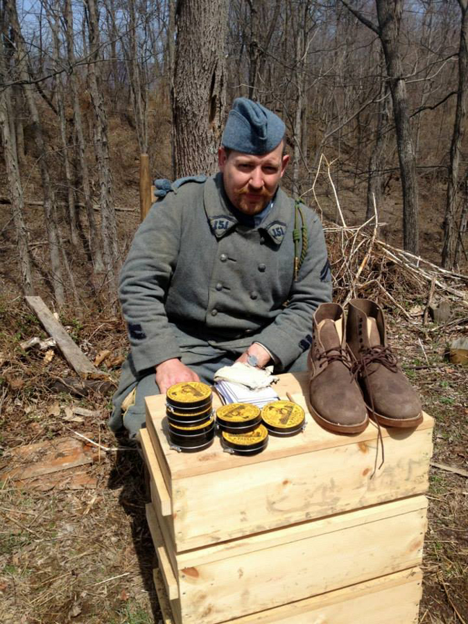 Cpl. Picard beside a distribution of shoe polish and boots, April 2014.