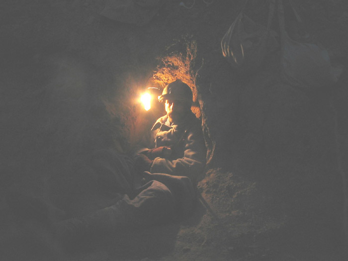 Sgt. Contamine in a small shelter uses a improvised lantern made from a sardine tin to see in the night.
