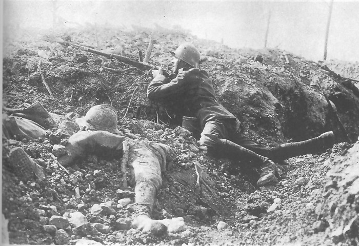German rifleman takes cover next to some half-buried French corpses.
