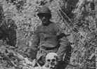 A French soldier wearing a mourning arm band poses beside a skull.